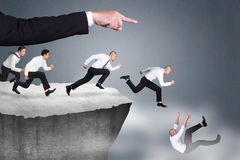 Bad Leader Give Wrong Direction. Bad direction in business concept. Big leader hand giving wrong direction causine his workers falling down at the edge of a royalty free stock image