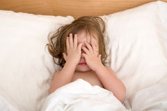 Bad Dreams. Toddler Girl closing her eyes in the bed, perhaps she is seeing bad dreams Royalty Free Stock Photography