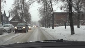 Bad driving conditions on city street. Bicyclist and cars on snowy frozen road