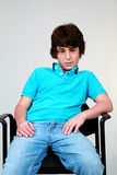 Bad Dude. Cute preteen boy in blue shirt seated Royalty Free Stock Images