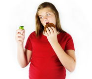 Bad Eater. Young girl holds in one hand, a cookie. In the other hand she holds a piece of broccolli. Looks like she chose the cookie Stock Images