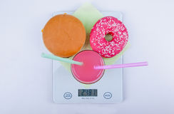 Bad eating habits. Hamburger, donut and soda drink on kitchen scales. Bad eating habit concept royalty free stock photos