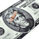 Bad Economy. US currency with bandage on it against white stock photos