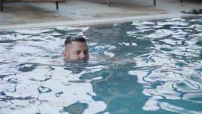 Bad för ung man i den inomhus pölen lager videofilmer