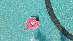 Bad f?r ung kvinna i havet i en simma cirkel Flicka som vilar i p?len p? en uppbl?sbar cirkel med en dator, ?verkant royaltyfri foto