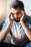 Sick troubled man sitting and having head ache. Bad feeling. Sick troubled beardful man sitting in the empty room holding hands near head and having head ache Royalty Free Stock Images