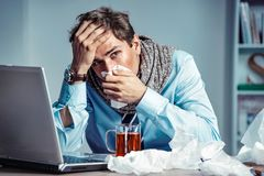 Bad feeling. Sick worker has high temperature. Photo of young man in office suffering virus of flu. Medical concept Royalty Free Stock Photos