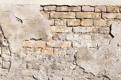 Bad foundation base on old house or building cracked plaster facade wall with brick background.  royalty free stock image