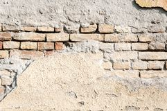 Bad foundation base on old house or building cracked plaster facade wall with brick background.  stock images
