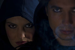 Bad girl and boy in gang with smoke. Gang members in the darkness with cigarette smoke around them,selective focus on woman face with hood,concept of bad boys royalty free stock photos