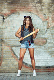 Bad girl holding a baseball bat. Bad girl with leather cat ears holding a baseball bat. Urban scene. Outdoor lifestyle portrait Stock Images