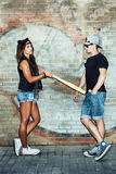 Bad girl with leather cat ears threatening baseball  bat guy. Stock Images
