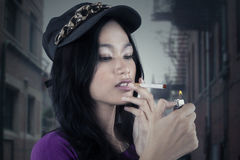 Bad girl lighting up a cigarette Stock Image