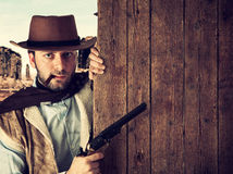 Bad gunman indicates with the gun a wooden plank Stock Photography