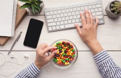 Bad habbit concept - eating candies instead of healthy food. Bad habit. Work space with laptop, candies and woman hands on white background, top view royalty free stock photography