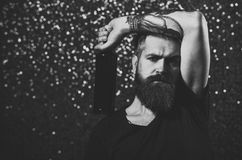 Bad habit, alcohol addiction. Hipster with long beard in black tshirt hold wine. Tattoo, fashion, style concept. Party, holidays celebration. Bearded man with royalty free stock images