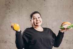 Bad habit. overweight pleasant cheerful girl trying to set a priority. Close up photo. health and body care royalty free stock images