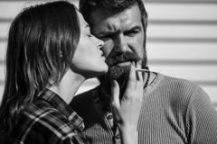Bad habit and relationship concept. Couple in love smokes together. Man and women with passionate faces on white stripy background. Girl gives cigarette to stock photography