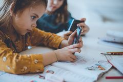 Bad habit. Two little girl using smart phone. Close up stock image