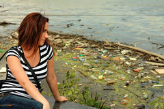 Girl looking at a polluted river Sava Stock Photos