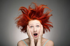Bad hair day. Redhead woman with messy hair against gray background royalty free stock photography