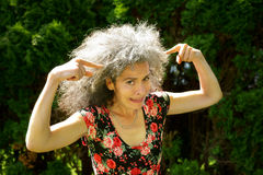 Bad Hair Day Panic Expression. Mature woman with a panicked expression on her face is pointing at her greying wild hair Royalty Free Stock Images