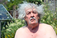 Bad hair day, a senior man. A senior man having a bad hair day with his grey hair untidy and sticking out. the man is sitting outside looking straight at the Royalty Free Stock Photography