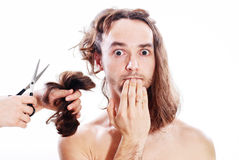 Bad haircut. Young frightened man with long hair being terribly clipped Royalty Free Stock Images