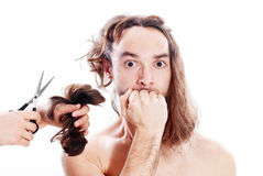 Bad haircut. Young frightened man with long hair being terribly clipped Stock Photography
