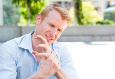 Bad hand pain. Closeup portrait, young man having acute bad joint pain in his hands, writer's cramp, massaging them, sitting in chair, isolated outdoors Stock Photos