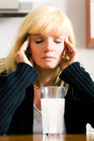 Really bad headache. Woman with a very bad hangover or migraine headache sitting in front of a glass of water with a painkiller Stock Image