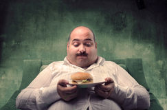 Bad health. Fat man sitting in an armchair and looking at a hamburger with sad expression Stock Photography