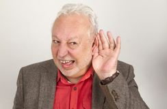 Bad hearing senior. Holding hand on his ear - on bright background Stock Photos