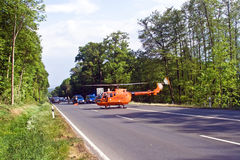 Rescue by Helicopter. BAD HOMBURG, GERMANY - May 05: Helicopter is landing on the street to save and transport a seriously insured person by car accident to Royalty Free Stock Image
