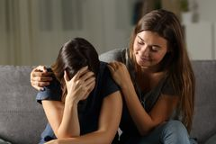 Bad hypocrite friend comforting a sad girl. Sitting on a couch in the living room at home Royalty Free Stock Images