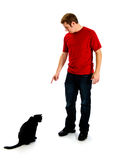 Bad kitty - man pointing at a black cat. Young man in a red shirt and jeans, is pointing down at a black cat who has his head down knowing he was misbehaving Royalty Free Stock Images