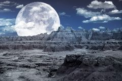 Bad Lands Fantasy. Rocky Moon Like Landscape and Huge Full Moon on the Cloudy Night Sky. Cool Abstract Design. Digital Art royalty free stock image