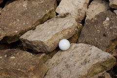 Bad lie 3. Golf ball in a bad lie off grass and into the rocks Stock Images
