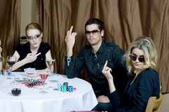 Bad losers. Attractive young caucasians, a man and two women, pose  with a defying expression, after losing a poker game Stock Images
