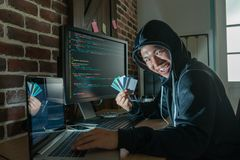 Bad man showing the stolen credit card. And breaking into the bank security system to get money royalty free stock images