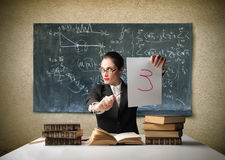 Bad mark. Portrait of a teacher sitting at a desk of a classroom and holding a paper sheet with a very bad mark on it royalty free stock photos