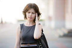 Bad memory. Portrait of young office woman walking on the street in summer, frowning with stressed, confused facial expression, holding her head with hand trying Stock Image