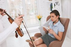 Negative delighted girl looking at her master. Bad mood. Upset young female sitting on chair while playing with her gadget stock image