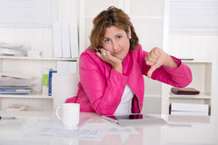Bad mood: woman in the office with thumb down Stock Photo