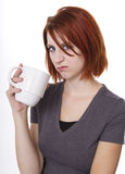 Bad Morning. Redhead woman expresses her displeasure while having a cup of Royalty Free Stock Image