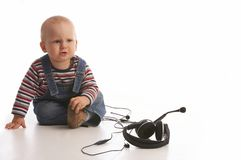 Bad music. Mad baby boy is playing with headset Stock Image