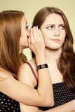 Bad news. One girl whispering to other some news. Surprised upset face and palm near face  second girl Stock Photography