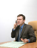 Bad news. Businessman talking on the cellphone is listening to the news royalty free stock image