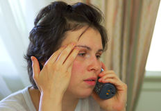 Bad news. A tired young woman receives bad news on the phone Stock Image