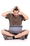 Bad news. Frustrated young man, holding his head and screaming, sitting with a laptop on white background Stock Images